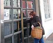 Eine Kundin betritt mit einem Korb voller Bücher den Haupteingang.