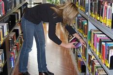 Eine Mitarbeiterin sortiert Romane in ein Regal ein.