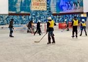 Auf dem Eis sind zahlreiche Kinder mit Eishockeyschlägern rund um ein Tor unterwegs, aber wo ist der Puck oder der Ball?