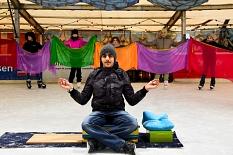 Im Hintergrund werden bunte Tücher gehalten, im Vordergrund sitzt ein junger Mann in der Pose eines Fakirs oder ähnlich, es fehlen aber die Nägel.©Universitätsstadt Marburg