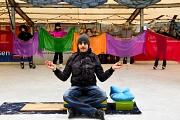 Im Hintergrund werden bunte Tücher gehalten, im Vordergrund sitzt ein junger Mann in der Pose eines Fakirs oder ähnlich, es fehlen aber die Nägel.