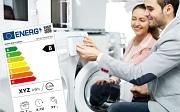 Es sind eine Frau und ein Mann zu sehen, die zusammen eine Waschmaschine bedienen. Dazu ist ein Energielabel eingeblendet.