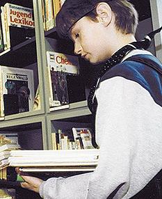"""Ein als Matrose verkleideter Schüler mit einem Stapel Bücher in der Hand auf """"Entdeckungsreise"""".©Universitätsstadt Marburg"""