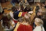 Ein Schüler öffnet eine geheimnisvolle Schatzkiste, aufmerksam beobachtet von anderen Kindern©Universitätsstadt Marburg