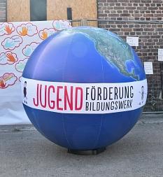 Ein riesiger Erdball mit dem Banner von Jugendförderung und -bildungswerk.©Universitätsstadt Marburg