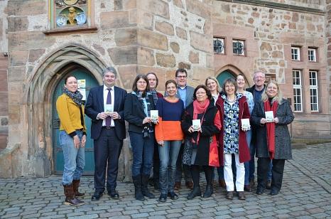 Bürgermeister Wieland Stötzel (2.v.l.) präsentiert das erste Marburger Klimasparbuch mit Marion Kühn (3.v.l.), Wiebke Smeulders (3.v.r.) und Vertreterinnen und Vertretern beteiligter Unternehmen: Kristall, Die Magie des Schönen; La Manufacture d'Anouk; Pr©Universitätsstadt Marburg