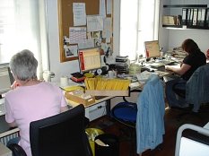 Zwei Mitarbeiterinnen sitzen an den Schreibtischen im Büro und bearbeiten Rechnungen.