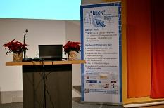 Ein leeres Rednerpult neben dem RollUp von *klick* Netzwerk Medienkompetenz©Universitätsstadt Marburg