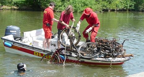Das Foto zeigt Freiwillige der DLRG, die ein Fahrrad aus der Lahn in ein Motorboot hieven.©DBM, Sonja Stender