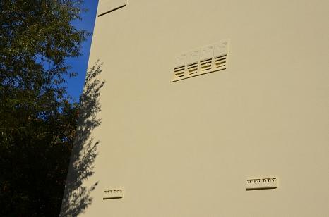 Mattgelbe Hausfassade, in die nebeneinander Fledermauskästen und in einigem Abstand darunter Sperlingsnisthilfen eingebaut wurden. Sie haben dieselbe Farbe wie die Fassade lockern den Fassadenanblick strukturell auf.
