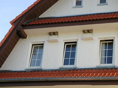 Hausfassade mit tonfarbigen Mehlschwalbennisthilfen und der Fassade farblich angepasste Kotbretter