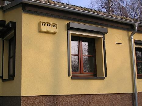 Mattgelbe Hausfassade mit einem Fledermauskasten und einer Sperlingsnisthilfe (beide in der ebenfalls mattgelb)