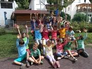 Viele Kinder haben sich zu einem Gruppenfoto zusammen gefunden und reißen die Arme in die Luft.