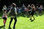 """Auf einer Wiese laufen Betreuer*innen und Kinder hinter einem Ball her, nach einem """"normalen Fußballspiel"""" sieht es nicht aus."""