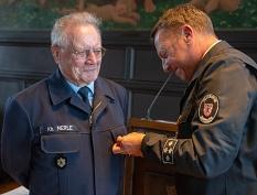 Karlheinz Merle erhält die Ehrenmedaille des Stadtfeuerwehrverbandes Marburg in Gold vom stellvertretenden Leiter der Marburger Feuerwehr, Andreas Brauer.©Patricia Grähling, Stadt Marburg