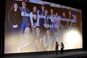 Vor der Kinoleinwand, auf die die Festivaljury projiziert ist, sieht man - eher klein - die Moderatorinnen der Preisverleihung Friederike Könitz (KiJuPa Marburg) und Birgit Peulings (Cineplex Marburg).