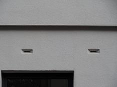Zwei schmale waagerechte Einflugritzen für Fledermäuse in einer Hausfassade (Nahaufnahme).
