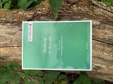 Auf einem breiten Ast, umgeben von grünen Blättern, liegt die Broschüre Marburg im Wandel©Universitätsstadt Marburg, Jochen Friedrich