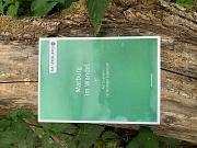 Auf einem breiten Ast, umgeben von grünen Blättern, liegt die Broschüre Marburg im Wandel