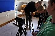 Eine Teamerin und 2 Teilnehmer stehen neben einem Stativ mit einer Kamera.