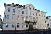 Vorderansicht der Stadtbücherei mit zahlreichen weißen Fenstern, großen Balkon und Vordereingang