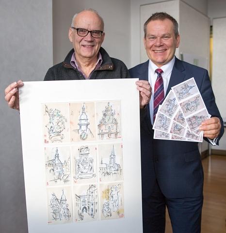Oberbürgermeister Dr. Thomas Spies (rechts) und der Künstler Richard Stumm präsentieren die Glückwunschkarte, die die Stadt Marburg 2018 verschicken wird. Daneben zeigt Stumm die neun Zeichnungen, die er insgesamt für die Stadt gestaltet hat.©Stadt Marburg, Patricia Grähling