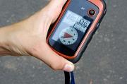 Ein orange-schwarzes GPS-Gerät wird in der Hand gehalten. Auf dem Display sieht man eine Kompassnadel
