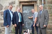Bürgermeister Wieland Stötzel (2. von links) zeigt zusammen mit (v.l.) Fachbereichsleiter Planen, Bauen, Umwelt Walter Ruth, DBM-Servicehofleiter Ralf Schmidt und DBM-Leiter Joachim Brunnet, mit welchen Techniken und Mitteln Graffiti entfernt werden könne