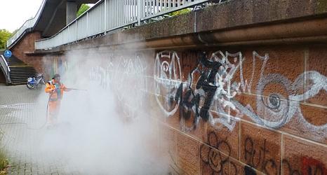 Das Foto zeigt einen Mitarbeiter des DBM bei der Beseitigung von Graffiti mit einem Dampfstrahler.©DBM, Sonja Stender