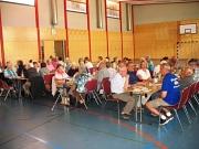 die Teilnehmer sitzen an Tischen in der Halle