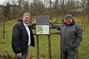 Bürgermeister Wieland Stötzel (links) und Ludwig Schneider, Ortsvorsteher Ockershausen, zeigen ein Schild des Apfellehrpfads im Heiligen Grund.