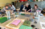 Gruppe von Teilnehmenden am Kurs Linoldruck 2019 bei Philipp Hennevogl an großem Tisch mit Druckutensilien