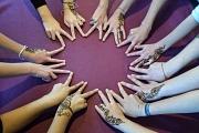 14 Hände im Kreis, die Finger zeigen zur Mitte, auf den Handrücken haben viele Hände Tattoos aus Henna.