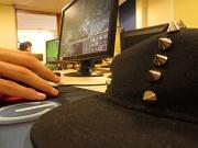 Eine Nahaufnahme zeigt eine Hand an einer Computermaus, im Hintergrund ein Monitor und vorne rechts eine Bascap.