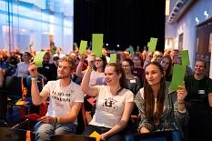 Ein großes Plenum macht eine Abstimmung, grüne Karten werden in die Luft gehalten.©Universitätsstadt Marburg