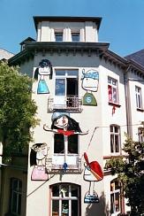 Die Fassade des Haus der Jugend, Ecke Frankfurter- / Friedrichsstraße: an der Wand sind 5 Köpfe angebracht. Sie sind etwa so groß, wie die Fenster und im Stile naiver oder kindlicher Kunst gemalt. Dieses Bild zeigt die Fassade nahezu in ganzer Größe.©Universitätsstadt Marburg