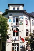 Die Fassade des Haus der Jugend, Ecke Frankfurter- / Friedrichsstraße: an der Wand sind 5 Köpfe angebracht. Sie sind etwa so groß, wie die Fenster und im Stile naiver oder kindlicher Kunst gemalt. Dieses Bild zeigt die Fassade nahezu in ganzer Größe.