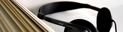 Aufgeschlagenes Buch mit einem schwarzen Kopfhörer©Universitätsstadt Marburg