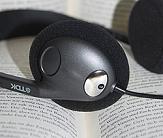 Ein schwarzer Kopfhörer liegt auf einem Buch mit aufgeschlagenen Seiten.©Universitätsstadt Marburg