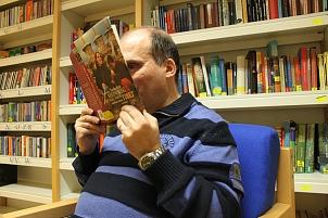 Ein Mann sitz in einem Sessel und hält ein aufgeschlagenes Buch direkt vor die Augen und versucht zu lesen.©blista / Troltenier