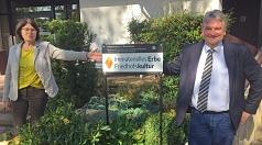 """Immaterielles Erbe Friedhofskultur: Bürgermeister Wieland Stötzel brachte gemeinsam mit Marion Kühn, Leiterin des Fachdienstes Stadtgrün und Friedhöfe, ein Schild an der neuen Friedhofskapelle am Rotenberg an, das den Hauptfriedhof als """"Immaterielles Erbe"""