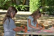 Zwei Mädchen basteln auf einem Tisch im Freien aus bunter Pappe und Federn Indianerschmuck.