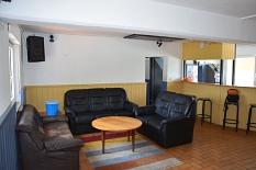 Ein Blick in das Jugendhaus in Wehrda, links eine Sitzgruppe mit Sofas und Tisch, rechts hinten die Theke mit Hockern.©Universitätsstadt Marburg