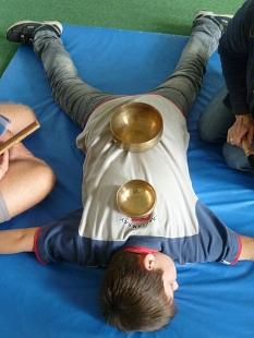 Ein Junge liegt auf einer Weichbodenmatte, auf seinem Rücken stehen zwei Klangschalen.©Universitätsstadt Marburg