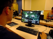 Ein Junge sitzt am Computer, im Hintergrund sind weitere Jugendliche an PCs zu sehen.