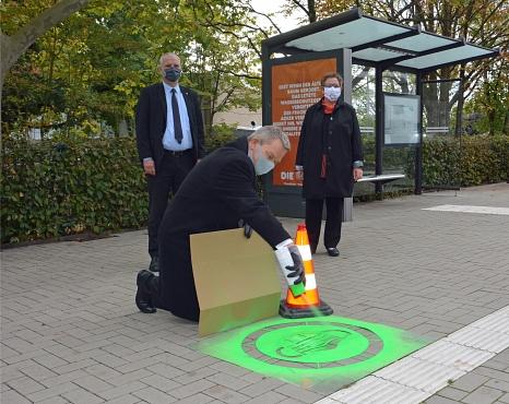 Oberbürgermeister Dr. Thomas Spies sprüht das Piktogramm mit dem Maskenmotiv auf den Gehweg vor der Haltestelle. Mit dabei ist Stadtwerke-Geschäftsführer Holger Armbrüster (hinten links) und Stadträtin Kirsten Dinnebier (hinten rechts).©Sarah Möller, Stadtwerke Marburg