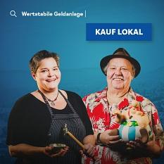 Katrin Semler von Juewelier Semler (l.) und Friedrich (Fiddy) Bode von Comics, Kitsch & Kunst (r.) auf dem Plakat der Kampagne Kauf lokal.©Universitätsstadt Marburg