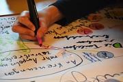 Man sieht eine Hand, die mit einem bunten Stift etwas auf ein großes Papier schreibt.