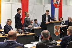 KiJuPa-Vorsitzender Manuel Greim am Rednerpult, links daneben Oberbürgermeister Dr. Thomas Spies, zahlreiche weitere Akteure bei der Sitzung der Stadtverordnetenversammlung am 23. Februar 2018.©Universitätsstadt Marburg