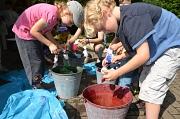 Kinder bearbeiten Textilien über Eimern mit farbiger Flüssigkeit